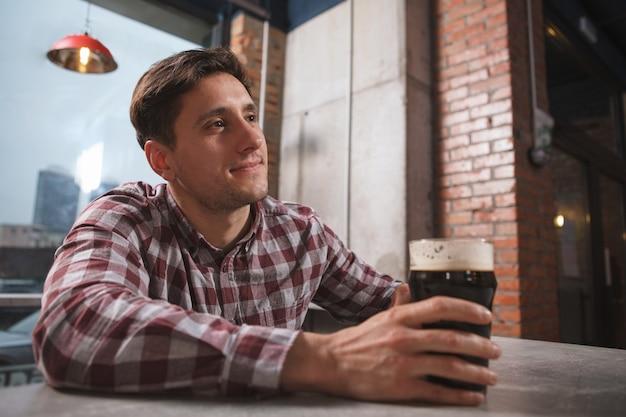 地元のパブでビールを飲むのを楽しんでいる魅力的なハンサムな男