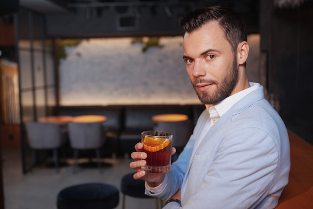 Charming handsome man looking to the camera confidently, enjoying his whiskey cocktail at the bar, copy space