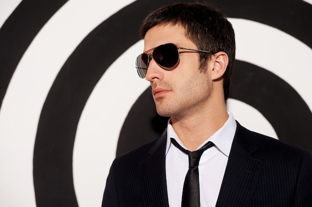 魅力的なハンサム。黒と白の背景に立って目をそらしている正装とサングラスのハンサムな若い男の肖像画