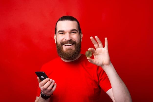 매력적인 잘 생긴 젊은 수염 난된 남자가 스마트 폰을 들고 붉은 벽에 bitcoin을 보여주는
