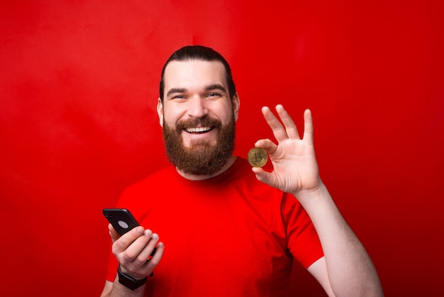 Charming handsome young bearded man holding smartphone and showing bitcoin over red wall