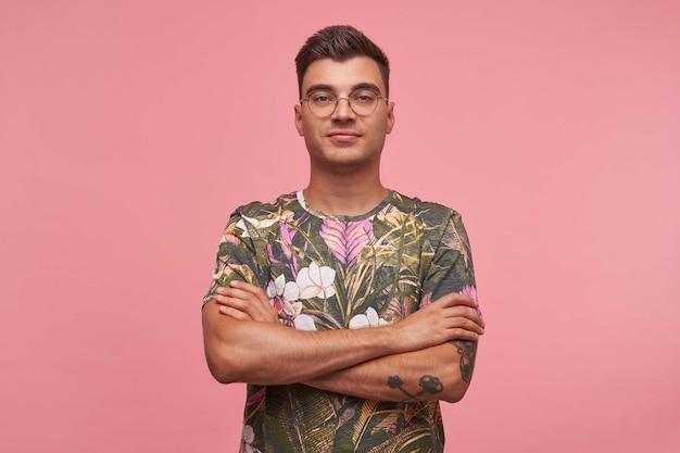自信を持ってポーズをとる魅力的なハンサムな若い男性、眼鏡と花のtシャツを着て、胸に腕を組んで