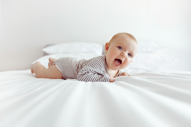 Charming happy baby on white bed