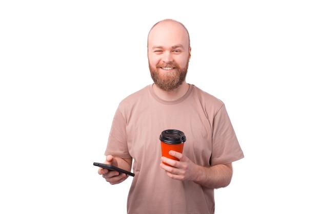 커피 종이 컵을 들고 스마트 폰 들고 매력적인 행복 수염 된 hipster 남자