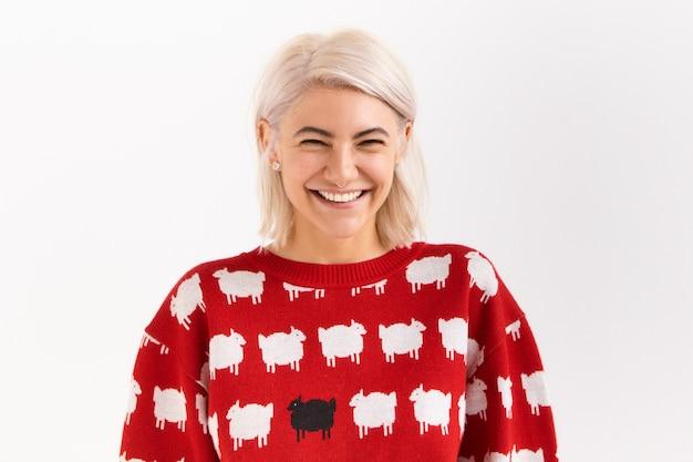 Affascinante giovane donna caucasica eccitata felice con capelli tinti di rosa in posa isolato che indossa un bel maglione rosso ridendo di uno scherzo divertente, sorridendo ampiamente, mostrando i suoi denti bianchi perfetti