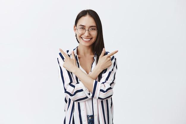 メガネとストライプのブラウスを着た魅力的な幸せな女性、胸に手を交差させ、幸せそうに笑いながら左右を指して、灰色の壁にポーズをとる