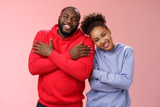 魅力的な幸せな誠実なアフリカ系アメリカ人の家族の男と女の子の関係は、腕を組んで胸を抱きしめ、ガールフレンドは痩せた彼氏の肩は素敵なカップルの笑顔は愛の暖かさを感じます