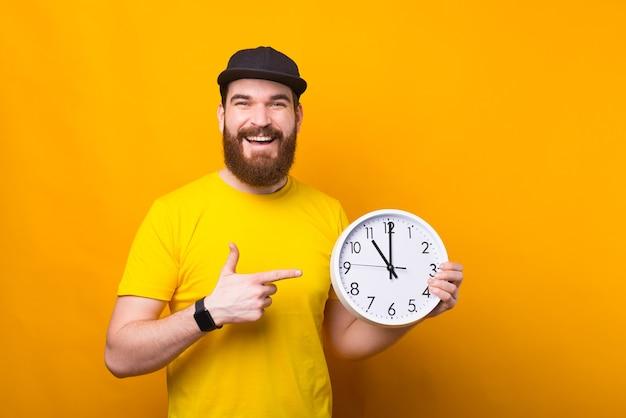 大きな白い時計を指している魅力的な幸せな笑顔のひげを生やしたヒップスターの男