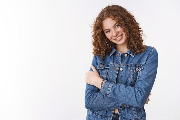 Affascinante felice sorridente ragazza rossa civettuola con lentiggini post cicatrici da acne lentiggini che indossa una giacca di jeans premere le mani strette abbracciando se stessa sensazione di freddo camminare fredda sera primaverile, sorridendo