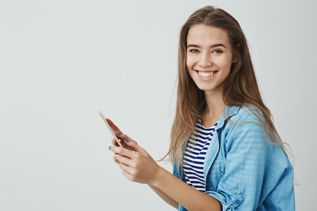 Charming happy smiling woman holding digital tablet enjoying using brand new gadget