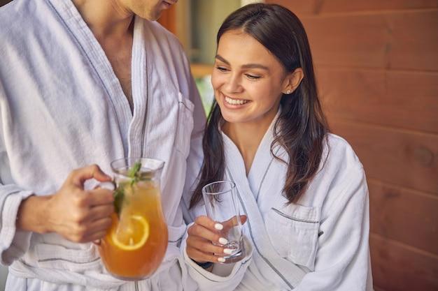 매력적인 행복 한 여자와 야외에서 시간을 보내는 흰색 부드러운 목욕 가운을 입고 남성