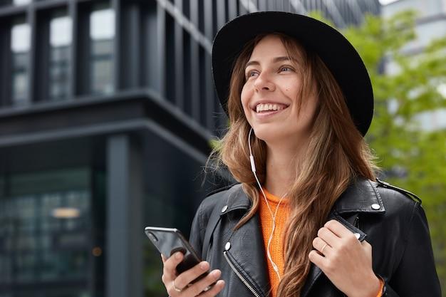 Affascinante donna felice naviga nel sito web con musica moderna, tiene il cellulare, usa gli auricolari, indossa un cappello nero