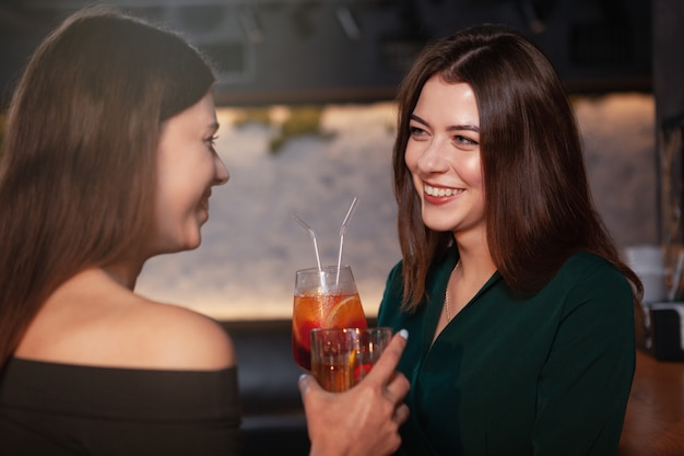 Charming happy woman laughing, talking to her friend at the bar while having cocktails together
