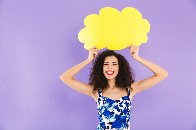Charming happy woman with curly hair in dress smiling and holding blank bubble above her head