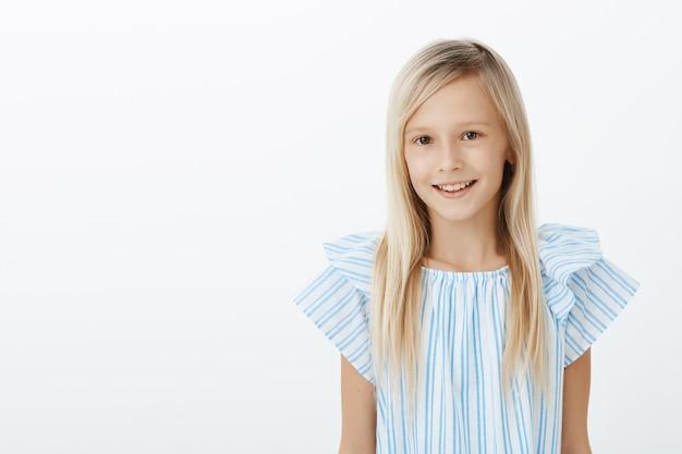 新しいクラスメートに自己紹介する魅力的な幸せな若い女の子。灰色の壁の上にさりげなく立って、フレンドリーな笑顔で、ブルーのブラウスにブロンドの髪を持つ満足しているのんきな愛らしい娘の肖像