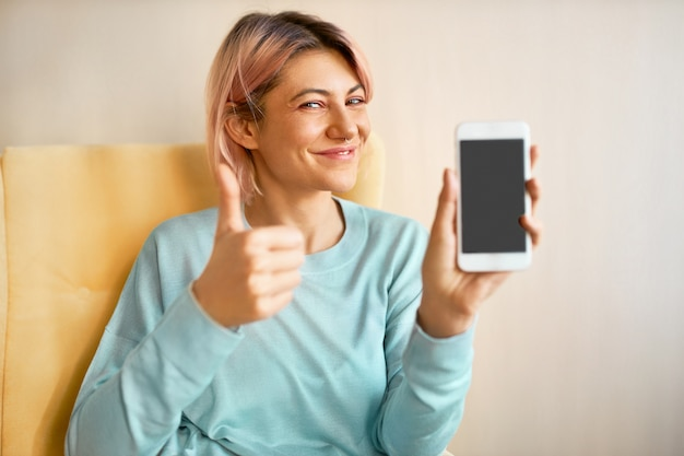Charming happy young woman with pinkish hair holding smart phone with blank black display with copy space for your advertising content, making thumbs up gesture as sign of appoval, winking at camera