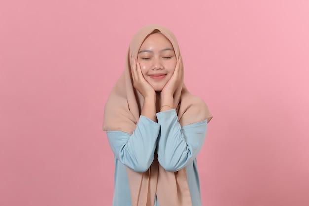 부드러운 표정을 가진 매력적인 히잡 아시아 소녀는 거친 뺨을 가지고 있으며 분홍색 배경에 히잡 포즈를 취한 뺨에 손을 대고 있습니다. 매력적인 아시아 이슬람 여성은 낭만적인 감정을 가지고 있습니다