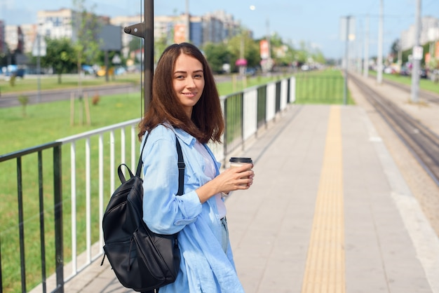 Charming hipster girl waiting for bus or tram on public transport station in the morning with cup of coffee.