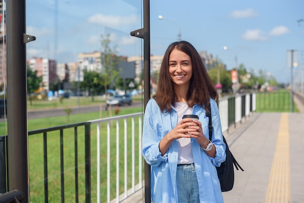 Charming hipster girl waiting for bus or tram on public transport station in the morning with cup of coffee