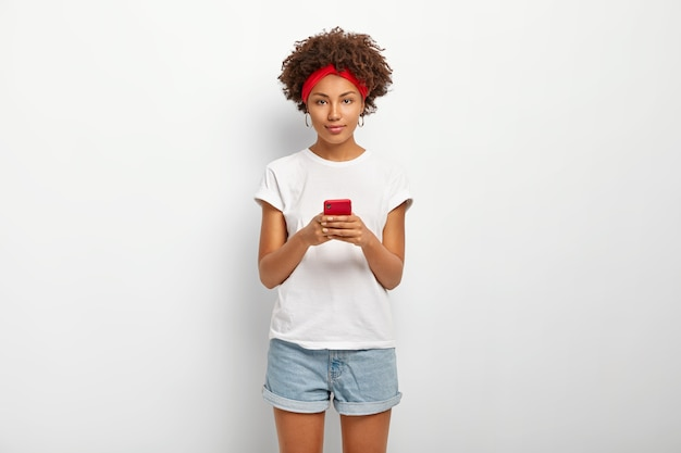 Charming hipster girl with afro hairstyle, types answer and reads feedback, being always in touch