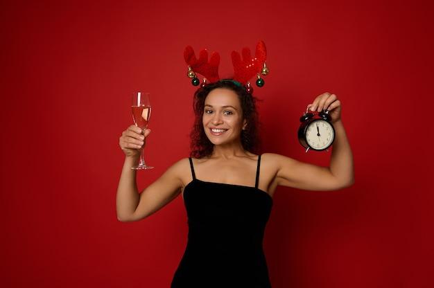 뿔 고리와 검은 벨벳 드레스를 입은 매력적인 히스패닉 여성은 알람 시계와 스파클링 와인을 곁들인 샴페인 플루트를 들고 카메라를 바라보며 이빨 미소를 짓고 있습니다. 크리스마스 새 해 개념