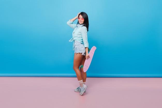 つま先に立ってピンクのスケートボードを持っているまっすぐな黒い髪の魅力的なヒスパニック系の女性。サングラスをかけたかなりアジアの女性モデルの屋内写真は、スポーツシューズとデニムのショートパンツを着ています。