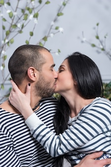 Charming international couple in striped sweaters kissing and hugging while sitting on the bed in the bedroom