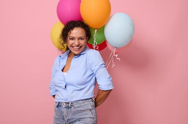 青いシャツを着た魅力的な楽しいアフリカの若い女性は、カメラを見て、背中の後ろに色とりどりの気球を持って、歯を見せる笑顔で笑って笑っています。ピンク色の背景、コピースペース