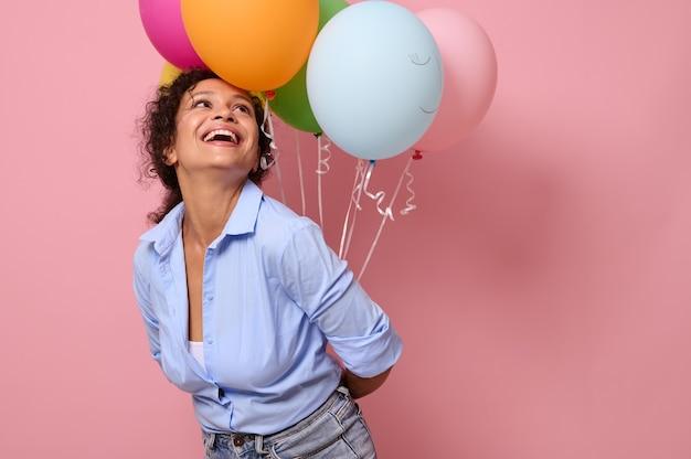青いシャツを着た魅力的な楽しいアフリカの若い女性は、背中の後ろで彼女の手にある色とりどりの気球を見上げて、歯を見せる笑顔で笑って笑っています。ピンク色の背景、コピースペース