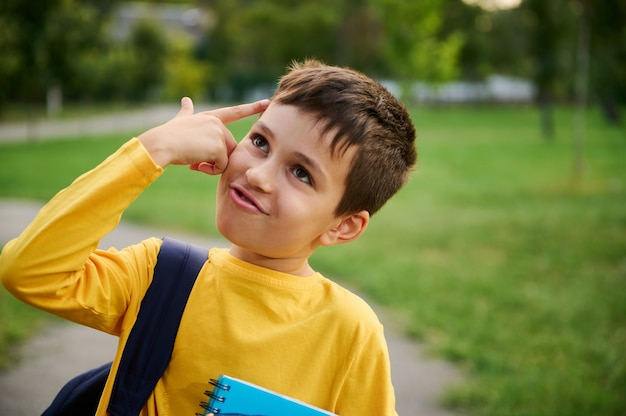 A charming joyful cheerful schoolboy holds his hand to his temple imitating a pistol, as a sign of tiredness from studying after a hard day at school, looking up in the city park background