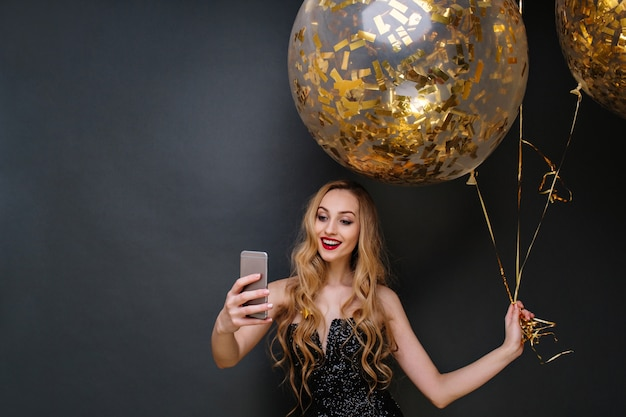 Charming joyful young attractive woman in black luxury dress, with long curly blonde hair making selfie with big balloons full with golden tinsels. celebrating modern party.