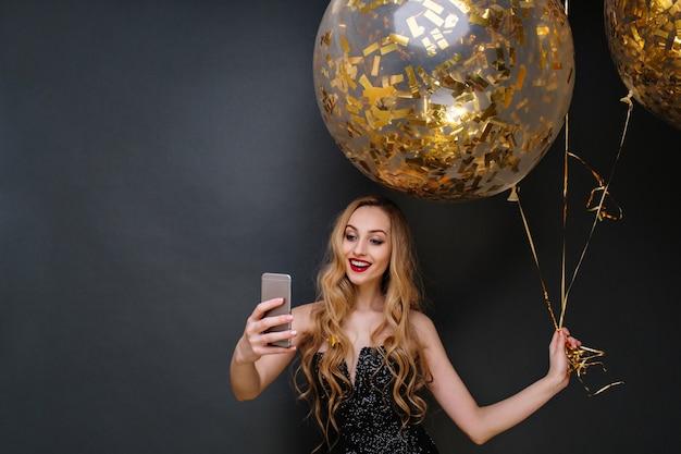黒の豪華なドレスを着た魅力的な楽しい若い魅力的な女性。長い巻き毛のブロンドの髪が、金色のティンセルでいっぱいの大きな風船で自分撮りをしています。現代のパーティーを祝う。