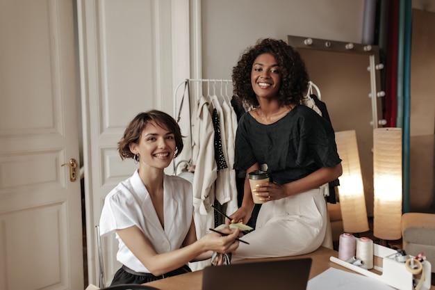 黒と白の衣装を着た魅力的な女性が笑顔で新しい服のデザインに取り組んでいます