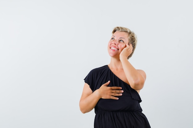 Affascinante signora in camicetta nera in posa come parlare al telefono e sembra allegra