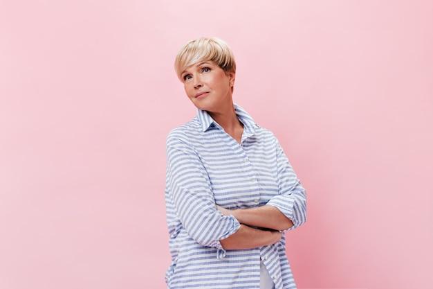 Affascinante signora in camicia blu in posa su sfondo rosa