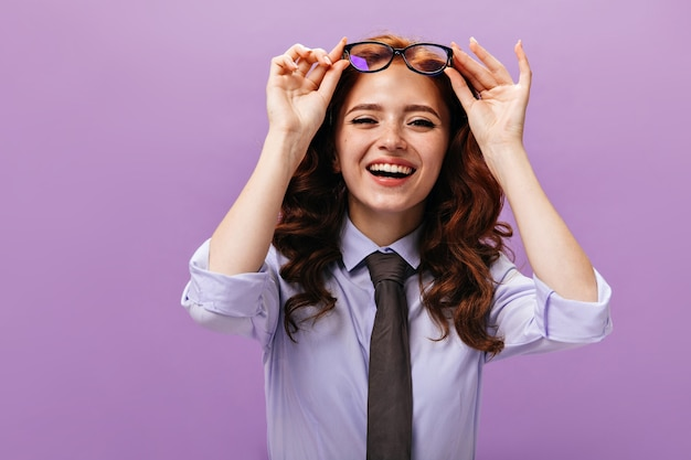 Charming lady in blue shirt taking off eyeglasses and laughing