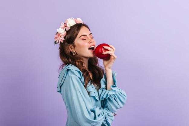 Affascinante signora in una corona di fiori morde una mela succosa. ritratto di ragazza in camicetta blu sulla parete lilla.