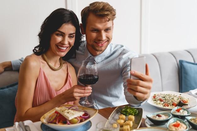 Очаровательная дама держит бокал вина и улыбается, пока джентльмен фотографирует со смартфоном