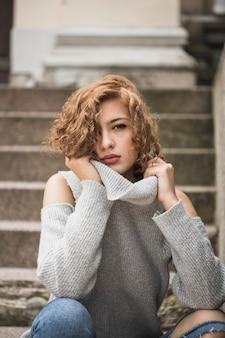 매력적인 여자 스웨터의 칼라를 잡고 계단에 앉아