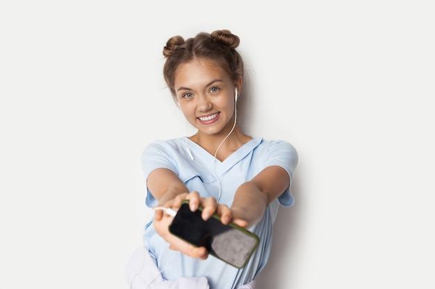 파란색 티셔츠에 매력적인 아가씨는 이어폰을 통해 음악을 듣고 흰 벽에 전화를 들고 미소 짓습니다.