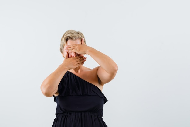 Очаровательная дама в черной блузке держится рукой за рот и глаза и выглядит застенчиво