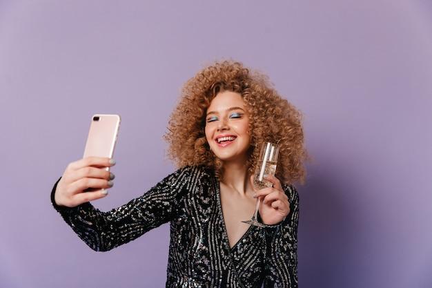 黒く輝くトップの魅力的な女性が笑い、目を閉じ、シャンパングラスを持って紫色の空間で自分撮りをします。
