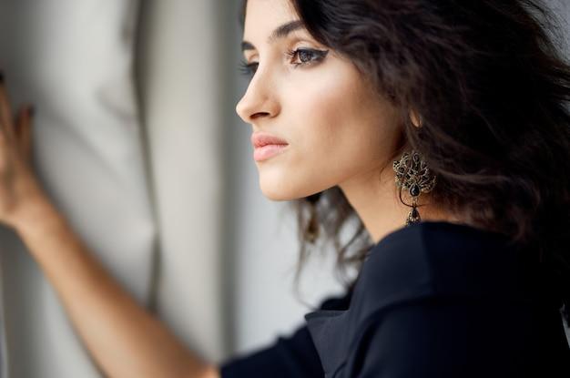 イブニングドレスの魅力的な女性が屋内の窓の近くに立って、ヘアスタイルのメイクモデル
