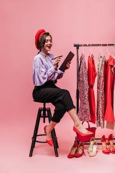 ファッショナブルなブラウスとズボンの魅力的な女性は、タブレットでメモを取ります。ドレスの背景にポーズをとる女の子。