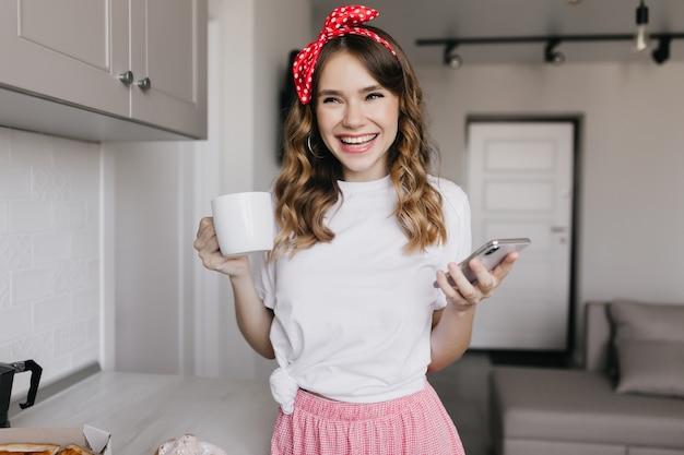 お茶を飲んで笑っている機嫌の良い魅力的な女性。コーヒーと電話でポーズをとる驚くべき巻き毛の女性の屋内ショット。