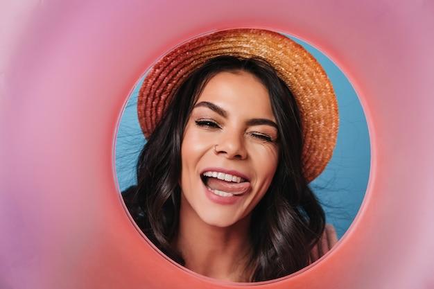 麦わら帽子の魅力的な女性が舌を出してポーズをとる