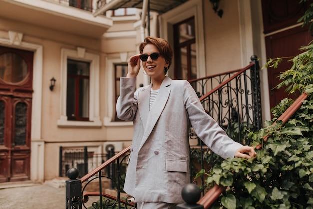 세련된 정장을 입은 매력적인 여성이 선글라스를 벗고 밖으로 걸어 나갑니다. 회색 재킷과 바지 반대 건물 미소에 젊은 여자