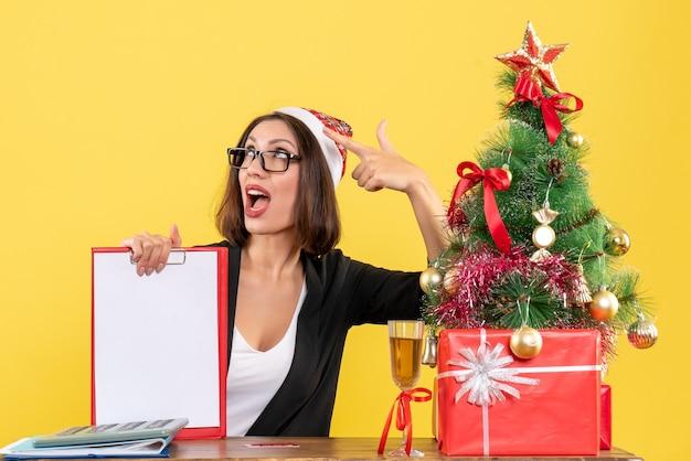 Очаровательная дама в костюме в шляпе санта-клауса и очках показывает документ, потрясенный в офисе
