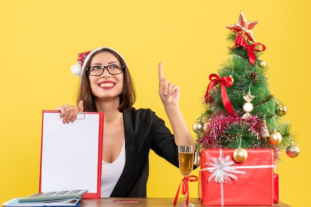 Очаровательная дама в костюме с шляпой санта-клауса и очками показывает документ, указывающий вверх в офисе на желтом изолированном