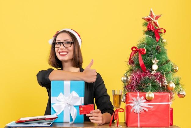 Очаровательная дама в костюме с шляпой санта-клауса и очками показывает подарок и банковскую карту, делая жест в офисе на желтом изолированном